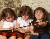 stock photo of triplets  - Triplets on the sofa playing with a violin - JPG