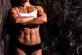 image of arm muscle  - Muscled woman against the scratched grunge background - JPG