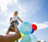foto of helium  - Mother lifting daughter holding colorful helium balloons against cloudy sky - JPG