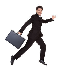 stock photo of bull rushes  - Successful businessman running with his briefcase hurrying along to an appointment full of energy isolated on white - JPG