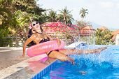 stock photo of flesh air  - Young woman in bikini and white sunglasses with pink inner tube having fun near pool - JPG