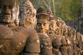 stock photo of carving  - Stone carved statues of Devas on the bridge to Angkor Thom in Angkor complex - JPG