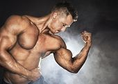 stock photo of pectorals  - Attractive male bodybuilder showing his biceps - JPG