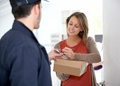 stock photo of receipt  - Woman sigining electronic receipt of delivered package  - JPG
