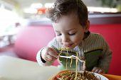stock photo of spaghetti  - The kid eating spaghetti in the restaurant - JPG