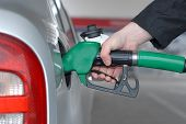 stock photo of high-octane  - Male hand refilling the car with fuel on a filling station - JPG