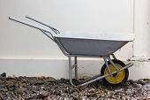 foto of wheelbarrow  - yellow wheelbarrow on wet river stones on white background - JPG
