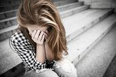 stock photo of teenagers  - Unhappy depressed teenager with face in hands sitting outdoor - JPG