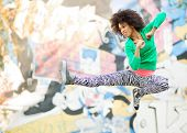 picture of empower  - Young woman kicking in mid air  - JPG