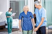 pic of male nurses  - Male nurse helping senior woman to use crutches with caretaker in background at nursing home - JPG