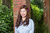 image of filipina  - Pinoy woman in a green garden on farm leaning against brick pillar - JPG