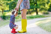 pic of woman boots  - Young mother and little adorable child girl in rubber boots having fun together family look in summer park on sunny warm day - JPG