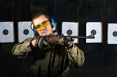 stock photo of shooting-range  - Man shooting with rifle at a target in shooting range - JPG