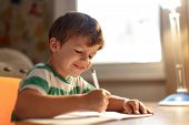 picture of writing  - Little boy write into exercise book education - JPG