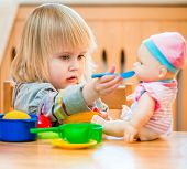 stock photo of child feeding  - girl feeding a doll at home in the children - JPG