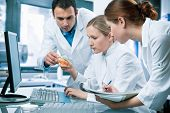 stock photo of beaker  - group of scientists working at the laboratory - JPG