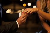 stock photo of night gown  - A closeup of a man putting an engagement ring on his girlfriend - JPG
