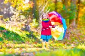picture of fall day  - Cute curly little girl wearing a warm red coat and rain boots playing with colorful umbrella enjoying a sunny autumn day in a beautiful fall park - JPG