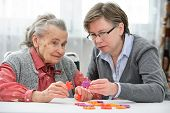 stock photo of nursing  - Elder care nurse playing jigsaw puzzle with senior woman in nursing home - JPG