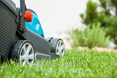 stock photo of grass-cutter  - Lawn mower on a green meadow - JPG