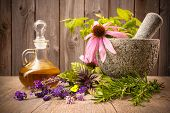 stock photo of wildflower  - Healing herbs with mortar and bottle of essential oil on wood - JPG