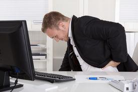 stock photo of sick kidney  - Businessman sitting at desk having pain at back - JPG