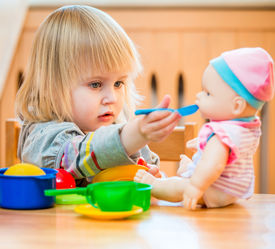 image of baby doll  - girl feeding a doll at home in the children - JPG