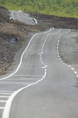 picture of bent over  - Curved asphalt road over volcanic lava - JPG