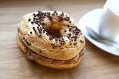 "stock photo of brest  - Cake ""Paris-Brest"" and coffee cup on a wooden table