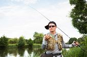 picture of sun perch  - Young man is fishing on the bank of the river - JPG