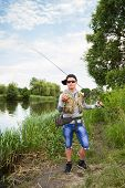 foto of sun perch  - Young man is fishing on the bank of the river - JPG