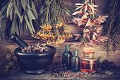 stock photo of mixture  - Vintage stylized photo of healing herbs bunches black mortar and oil bottles herbal medicine - JPG