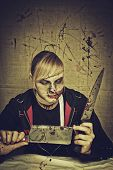 picture of gory  - Sinister maniac with two knives over bloody background - JPG