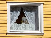 stock photo of lace-curtain  - window in a wooden house with white laced curtains - JPG