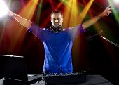 pic of emcee  - caucasian male dj playing mp3 music with computer and mixer - JPG