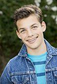 picture of denim wear  - Smiling teenage boy outside wearing denim jacket vertical format 13 yrs old - JPG