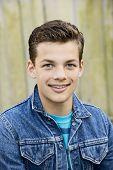 stock photo of denim wear  - Smiling teenage boy outside wearing denim jacket vertical format 13 yrs old - JPG