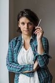 stock photo of smoking woman  - Young woman in plaid shirt smoking next to window - JPG