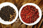 stock photo of peppercorns  - red peppercorns seeds and black pepper on wooden background - JPG