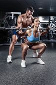 stock photo of squatting  - beautiful young sporty sexy couple doing squat workout in gym - JPG