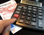 stock photo of profit  - concept of profit on a calculator with bank notes - JPG