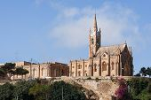 stock photo of gozo  - Mgarr harbor with view on church to Our Lady of Lourdes on top of the hill - JPG