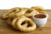 picture of dipping  - Heap of deep fried onion or calamari rings with chilli dip on wood board - JPG