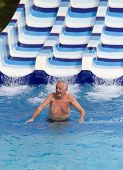 image of toboggan  - Senior man enjoying holiday in aqua park - JPG
