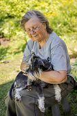 stock photo of schnauzer  - Senior woman hugs her black and silver miniature schnauzer dog in countryside - JPG