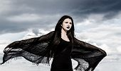 stock photo of flutter  - Young woman in a black fluttered clothes over the stormy sky - JPG