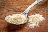 image of tablespoon  - tablespoon of whey protein powder against rustic scratched wood background - JPG