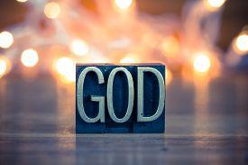 foto of godly  - The word GOD written in vintage metal letterpress type on a soft backlit background - JPG