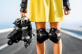 foto of up-skirt  - Sport woman in yellow skirt and protection wear holding rollers on the highway - JPG