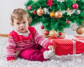 stock photo of new years baby  - Adorable baby with Christmas gift and winter tree with New Year decoration at home - JPG
